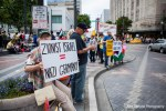 A demonstrator holds a controversial sign during a protest in solidarity with those affected by violence in Palestine.