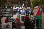 Pro Israel activists can been seen draped in Israeli flags as pro Palestine supporters look on.