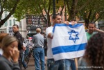 Pro Palestine supporters can be seen in the background as pro Israel supporters show solidarity by holding a rally in Occidental Park, Seattle.