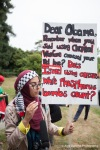 An activist is interviewed during a protest as President Obama arrives in Seattle for a fundraising dinner.