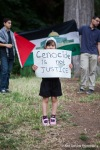 A child holds a sign in front of a Palestinian flag during a demonstration along the route to be traveled by President Obama as she stops in Seattle for a fundraiser.