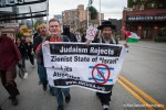 Demonstrators carry signs protesting Israeli Zionism as they march past Starbucks in Seattle