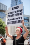 A demonstrator holds a sign protesting violence in Palestine.
