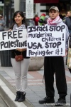 Demonstrators hold signs at Westlake Park during a pro Palestine rally in Seattle, WA